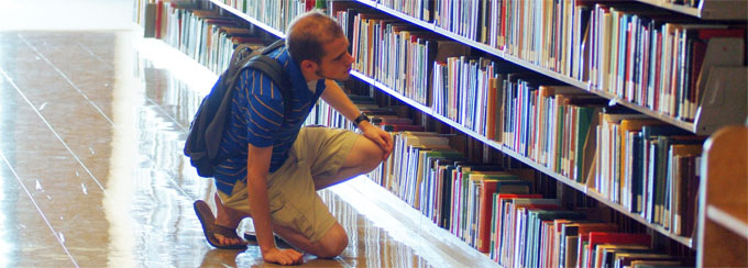 Student searching book stacks in the libarary.